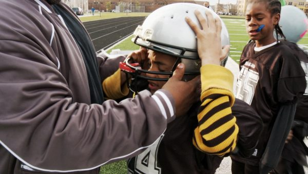 """Donning a football helmet, an accessory in a sport known for its concussions, in """"Head Games."""" Credit Variance Films"""